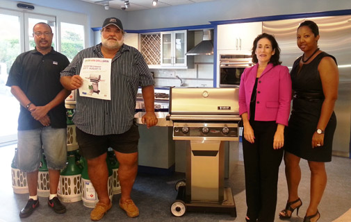 Mr. Jonathan Boyles (Bermuda Gas Distribution Manager), Mrs. Judith Uddin (Bermuda Gas General Manager), and Mrs. Angel Smith (RUBiS Energy Sales and Marketing Representative), presenting Mr. Dean Jones (wearing hat) with his new stainless steel barbecue.