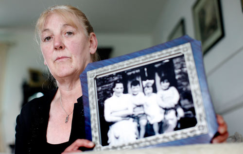 Helen McKendry, eldest daughter of murdered woman Jean McConville, holds a family photograph showing her mother Jean McConville, left, and some of Jean's children including Helen herself, second right. *AFP photo/ Peter Muhly