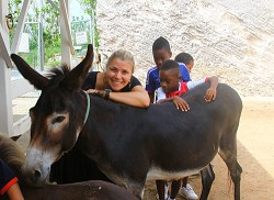 Erica Fulton, WindReach's new executive director, derives obvious pleasure helping these children feel at ease around a donkey. *Photo by Lance Furbert