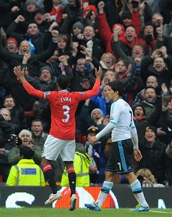 How sweet it is: Manchester United captain Patrice Evra celebrates a victory over Liverpool as Liverpool's Luis Suarez walks past him. Suarez refused to shake Evra's hand before the start of the match between the two clubs after serving an eight game ban for racially abusing Evra. *AFP photo